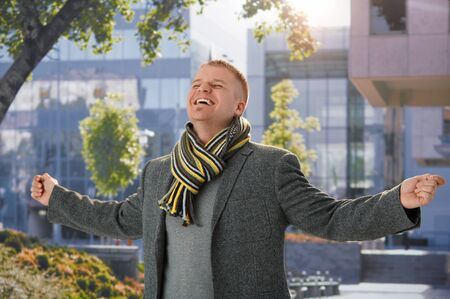 outspreading: Happy guy standing in spring sunshine outside of building, with arms wide open, laughing with closed eyes. Stock Photo