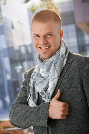Happy man wearing trendy scarf giving thumb up, smiling at camera, outdoors. photo