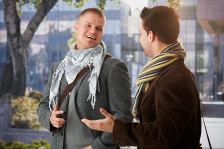 amigas conversando: Dos amigos de pie fuera del edificio, charlando, riendo. Foto de archivo