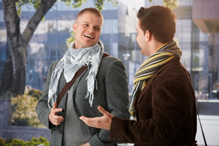 Two friends standing outside of building, chatting, laughing. photo