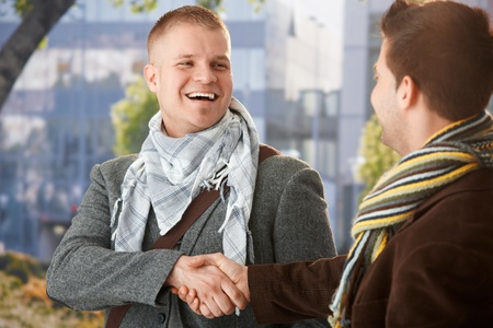 two friends: Happy young men shaking hand in greeting, laughing, standing outdoors in trendy clothes.