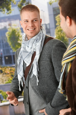 Smiling young men talking outside, wearing trendy spring clothes. Stock Photo - 10427498