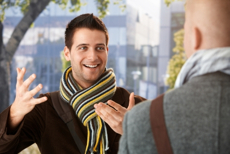 Cheerful guy gesturing to friend in conversation, standing outdoors, wearing scarf, smiling. photo