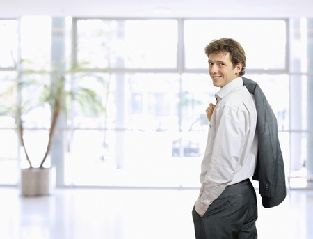 draped: Young businessman standing in confident pose with hands in pocket and his suit draped over his shoulder. Looking back, smiling.