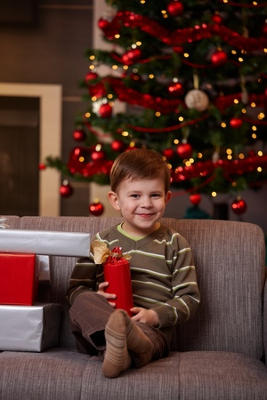 boys only: Portrait of happy little boy sitting on couch with christmas presents, smiling. Stock Photo