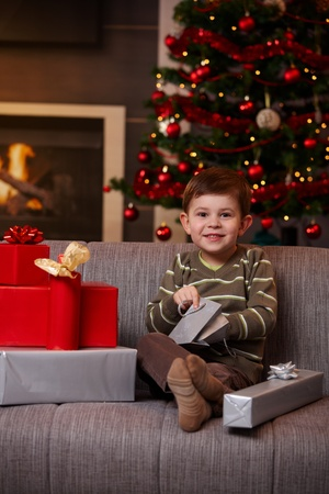 Portrait of happy little boy sitting on couch opening christmas presents, smiling. photo