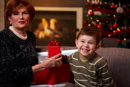 Happy grandmother and grandchild sitting on sofa at home, holding christmas gift, smiling. photo