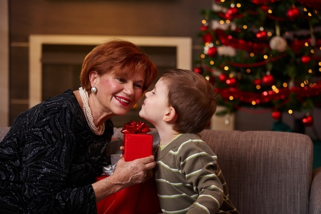 looking at each other: Little boy leaning to smiling grandmother with eyes closed, getting surprise christmas present.
