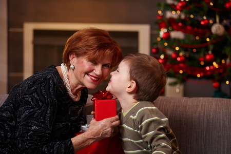 Small boy getting christmas present from happy grandmother, giving a kiss.   photo