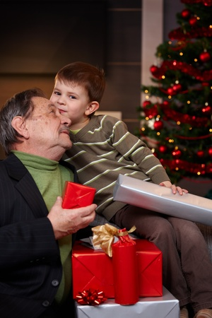 Portrait if happy grandfather and grandson holding christmas presents, cuddling.         photo