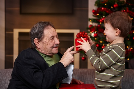 giving season: Small boy giving present to grandfather at christmas, smiling.