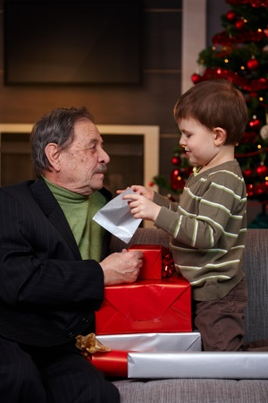 Small boy getting christmas present from grandfather, looking into bag.   photo