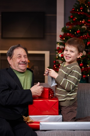 Small boy giving christmas present to happy grandfather, smiling.   photo