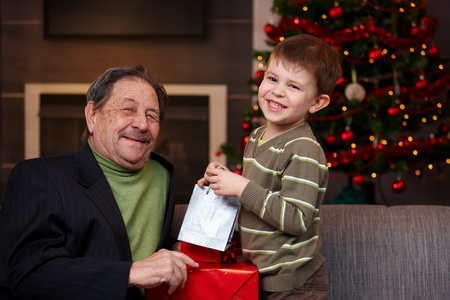 Young boy giving christmas present to happy grandfather, smiling.   photo