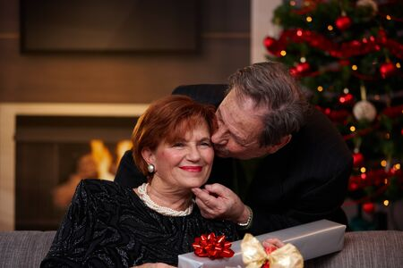 getting together: Happy senior woman getting christmas present, smiling. Husband kissing her on the cheek.   Stock Photo