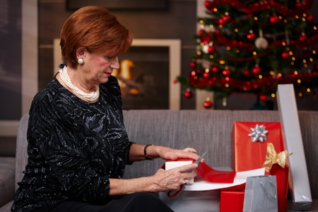 one senior woman only: Senior woman sitting on couch at home, wrapping christmas gifts, cutting paper with scissors.