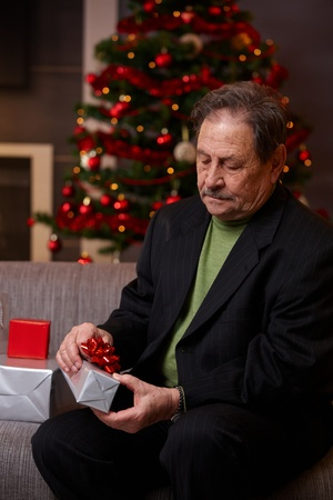 Senior man sitting on couch at home, wrapping christmas gift, concentrating.