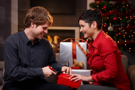 Happy young couple preparing for christmas, wrapping gifts, smiling.   photo