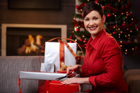 Happy young woman sitting on couch at home, wrapping christmas presents, smiling.   photo