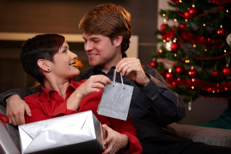 getting together: Happy young man giving christmas present to his girlfriend, smiling.