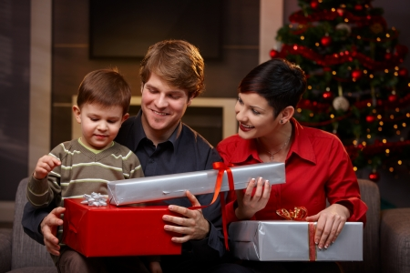 three gift boxes: Happy parents giving christmas gifts to their son, smiling.