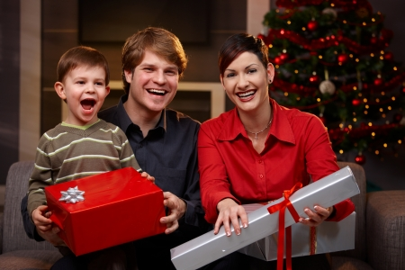 three presents: Portrait of happy family sitting at couch, holding christmas gifts, laughing.