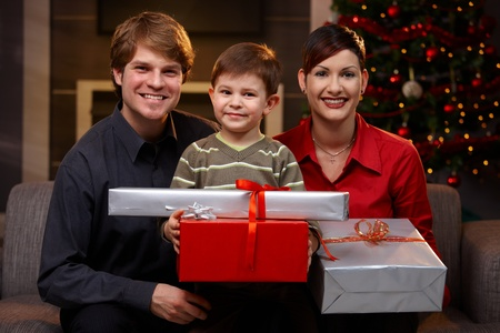 Portrait happy young couple and son at christmas, holding presents, smiling. photo