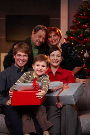 4 years old: Portrait of happy family at christmas, sitting on sofa, holding presents, smiling. Stock Photo