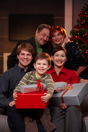 five years old: Portrait of happy family at christmas eve, holding presents, smiling.
