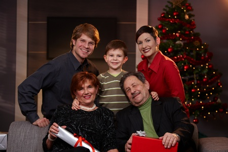 70s adult: Portrait of young couple and son with grandparents at christmas, smiling.