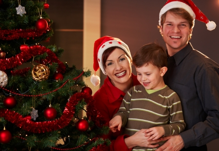 Happy parents holding small child at christmas tree, boy pointing at tree. photo