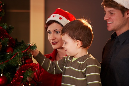 Family looking at christmas tree at home, celebrating together. photo
