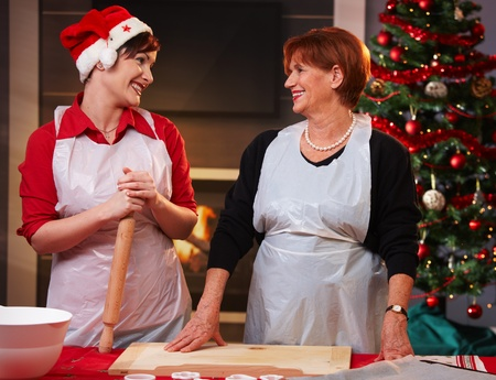 Mother and daughter smiling at each other while baking christmas cake. photo