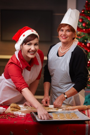 Portrait of happy mum and daughter at christmas baking at home. photo