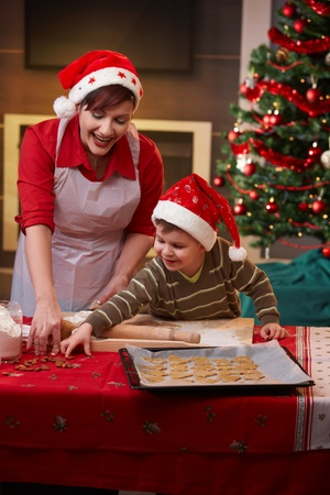 Mother and small son making christmas cake together at home. photo
