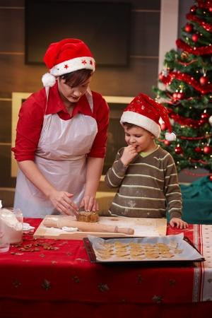 decoracion de pasteles: Madre e hijo pequeño está preparando para la Navidad, la torta de hornear.