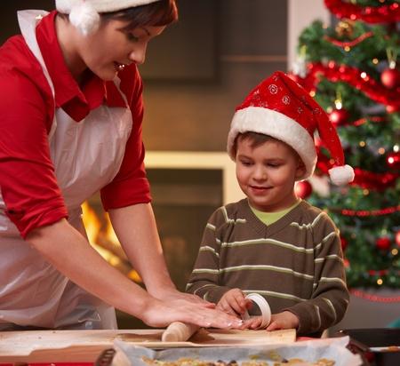 haciendo pan: Madre e hijo haciendo pastel de Navidad, hijo de madre viendo mano, sonriente.
