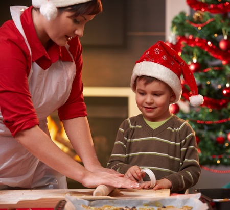 weihnachtskuchen: Mutter und Sohn machen Weihnachtskuchen, der Sohn gerade Mamas Hand, lächelnd.