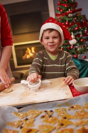 galletas de jengibre: Niño para ayudar a hornear pasteles de Navidad, sonriendo a la cámara.