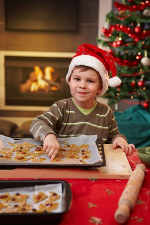 Portrait of small child smiling at camera, reaching for christmas cake in baking pan. photo