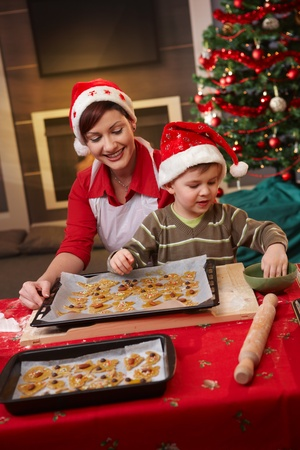 small cake: Smiling mum and small son decorating christmas cake together at table. Stock Photo