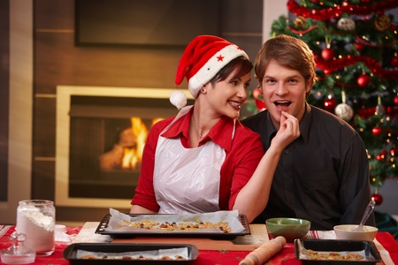 Smiling woman handing christmas cake to man for tasting. photo