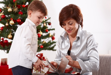 45 years old: Grandmother and grandson opening christmas presents together, smiling. Stock Photo