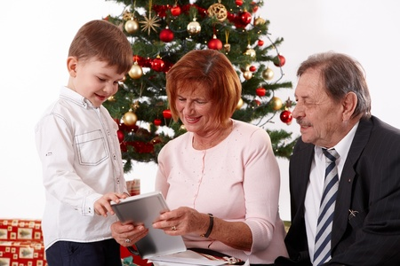 Happy small boy with grandparents at christmas looking at present, smiling. Stock Photo - 10533318