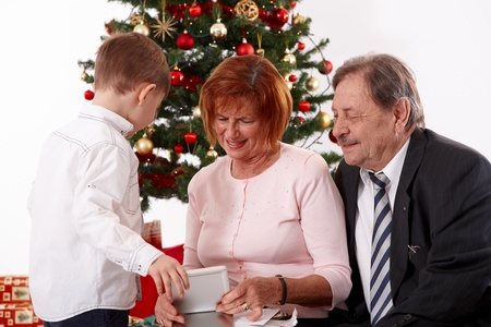Grandparents with grandson at christmas, looking at presents together. photo