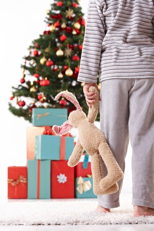 home decorating: Little boy going in pyjama to unwrap gifts on christmas morning, holding toy.