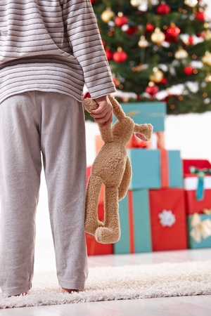 soft toy: Little boy standing with toy handheld in pyjama at christmas tree full of presents on christmas morning. Stock Photo