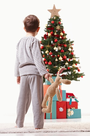 Little kid wearing pyjama, holding cute toy, looking at huge christmas tree and presents. photo