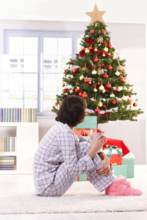 holding a christmas ornament: Woman in pyjama having coffee on christmas morning, looking at tree. Stock Photo
