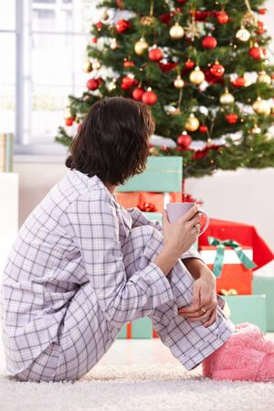 christmas morning: Woman in pyjama sitting on floor on Christmas morning, drinking coffee, looking at tree and gifts.